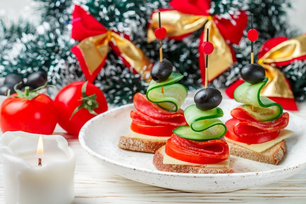 Delicatessen appetizer of bread, cheese, salami sausage, fresh tomatoes and cucumbers, black olives