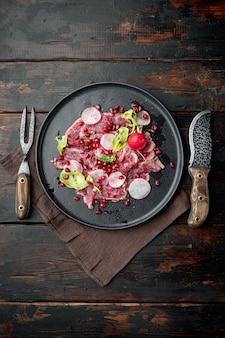 신선한 마블링 고기로 만든 델리카트슨 전채 - 쇠고기 카르파초 세트, 무와 가닛, 접시, 오래된 어두운 나무 테이블 배경, 위쪽 전망 평면, 텍스트 복사 공간