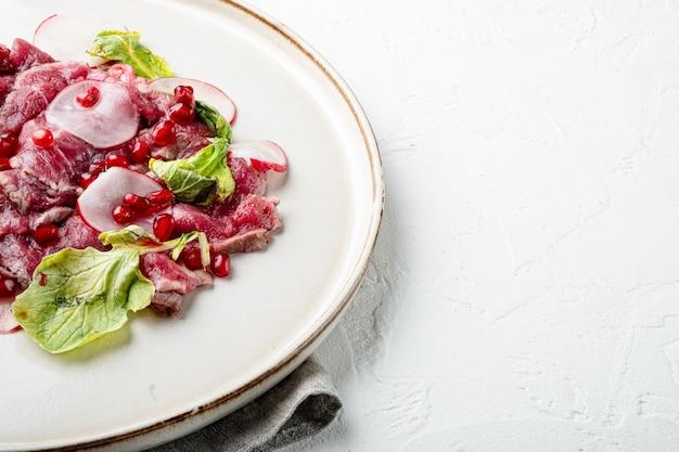 신선한 마블링 고기의 델리카테센 전채 - 쇠고기 카르파초 세트, 무와 석류석, 접시, 흰 돌 배경, 텍스트 복사 공간