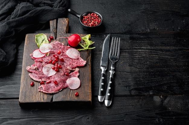 新鮮な霜降り肉のデリカテッセン前菜-大根とガーネットを添えた牛肉のカルパッチョセット、木製のサービングボード、黒い木製のテーブルの背景、テキスト用のコピースペース