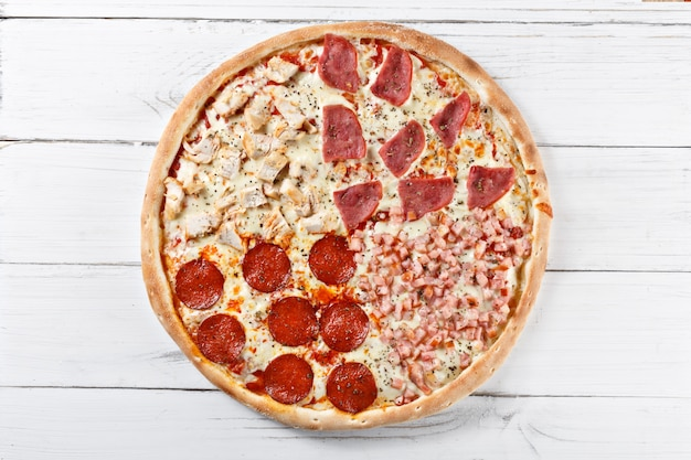 Delicious 4 in 1 fresh pizza with different kind of meat served on wooden table. top view.