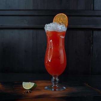 나이트 클럽의 테이블에 신선한 오렌지와 라임 조각이있는 천연 크랜베리 주스가 추가 된 보드카와 화이트 럼이 들어있는 유리에 맛있는 알콜 칵테일