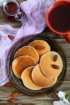 木製のテーブルにお茶とジャムを添えたおいしいアーモンドのパンケーキ。上面図。