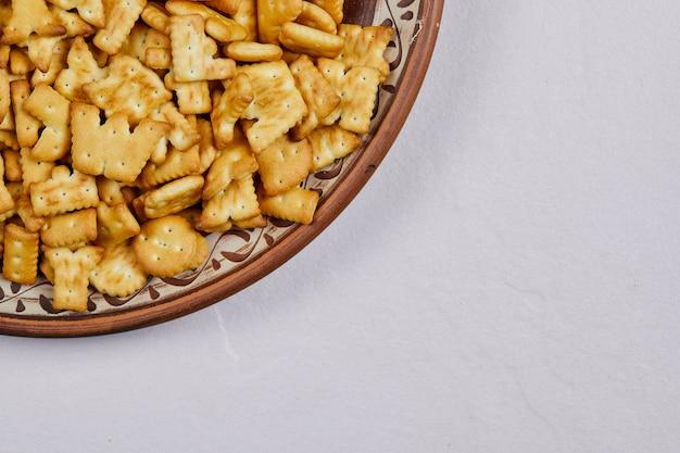 Вкусные крекеры алфавита на керамической тарелке.