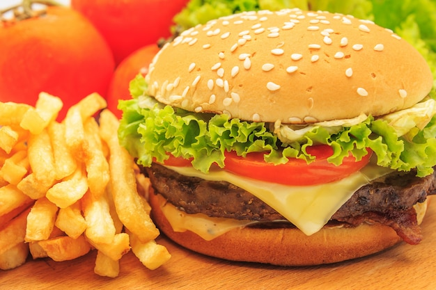 Delicious american cheeseburger with french fries, fresh lettuce and tomato