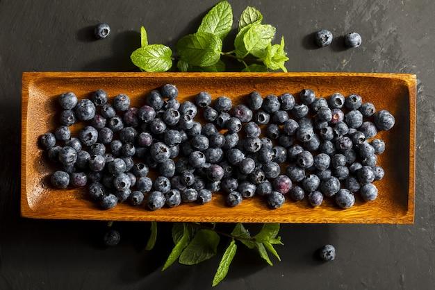 Вкусные и аппетитные ягоды черники на подносе из черного дерева и листья мяты (мята перечная, мята)