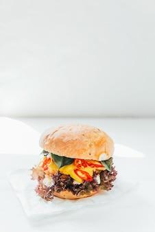 白い木製の背景にチキンカトレット、バジル、唐辛子と美味しくて食欲をそそるハンバーガー