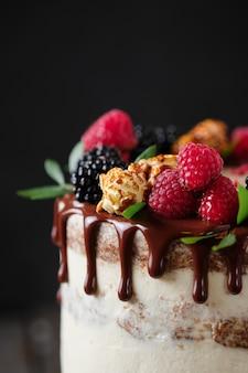 Вкусный и красивый торт ручной работы. кондитерские изделия к празднику. десерт украшен свежими ягодами, зелеными листьями и сладостями.