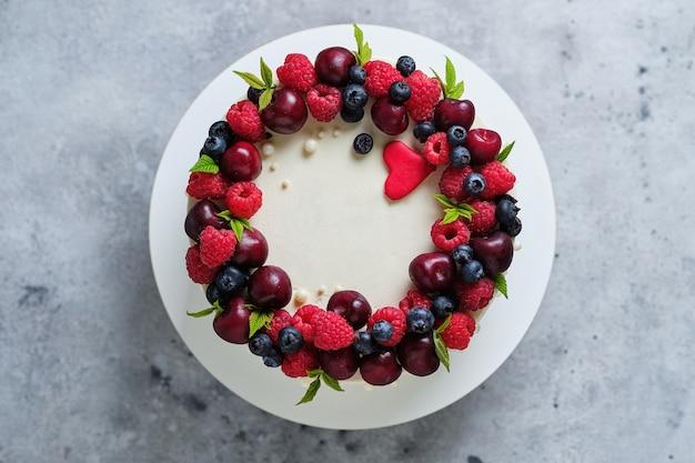 Вкусный и красивый торт ручной работы. кондитерские изделия к празднику. десерт украшен свежей малиной, вишней и черникой.