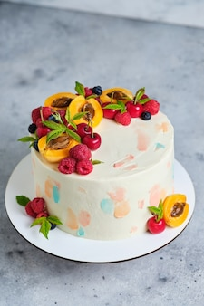 Вкусный и красивый летний торт ручной работы. кондитерские изделия к празднику. десерт украшен свежими ягодами и фруктами.