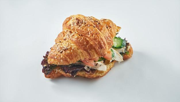 Вкусный и полезный завтрак - круассан с курицей, помидорами, листьями салата и сливочным сыром на белой тарелке. выборочный фокус