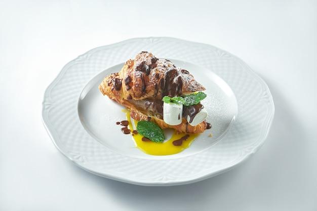 Вкусный и полезный завтрак - сладкий круассан с бананом, шоколад на белой тарелке. выборочный фокус