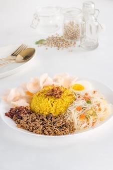 Вкусная и здоровая индонезийская еда в белой тарелке с золотой вилкой и ложкой на белом фоне