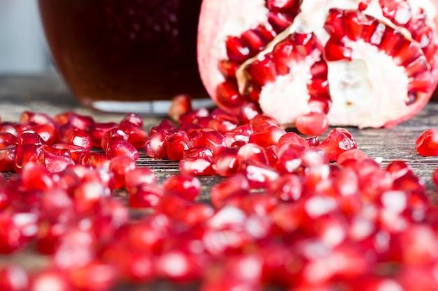 맛있고 건강한 석류는 붉은 씨앗, 붉은 곡물이 있는 붉은 과일 석류, 신선한 석류 클로즈업으로 여러 부분으로 나뉩니다.