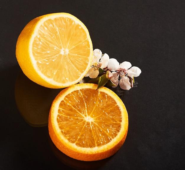 Вкусный и сочный апельсин и лимон, изолированные на черном.