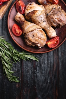 Вкусный и сытный ужин для всей семьи, несколько кусочков курицы на тарелке, голени на гриле, овощи и специи