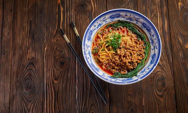 木製のテーブルに黒い箸が付いた伝統的な青いボウルのおいしくてスパイシーな自家製四川ライスヌードル、メニューデザインのためのアジア料理のコンセプトコピースペース