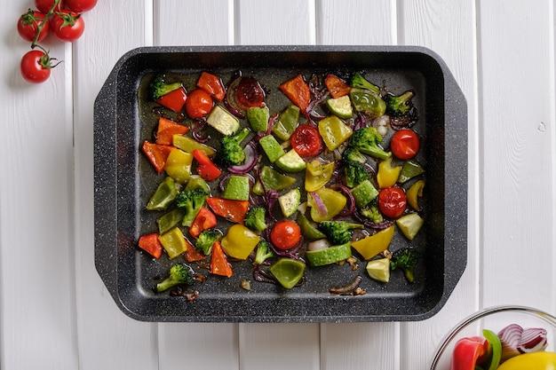 Вкусная и полезная еда. жареные овощи в форме для запекания на белом деревенском столе крупным планом