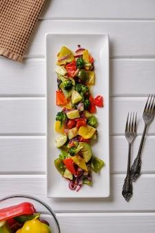 Вкусная и полезная еда. жареные овощи на белой тарелке на белом ржавом столе крупным планом