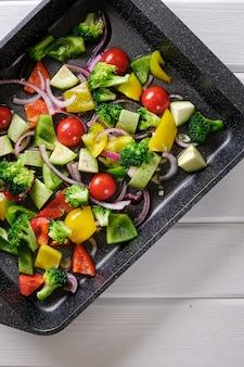 Вкусная и полезная еда. свежие сырые овощи в форме для запекания на белом ржавом столе крупным планом