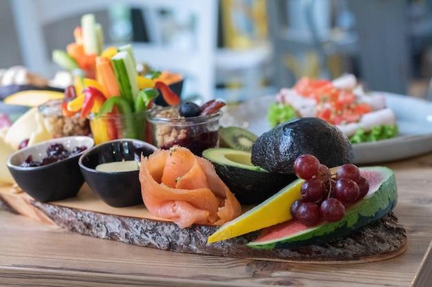 나무 판자에 맛있고 다양한 얇게 썬 과일과 채소