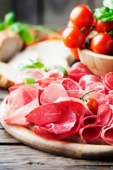 Delicious antipasto with ham and bresaola, selective focus