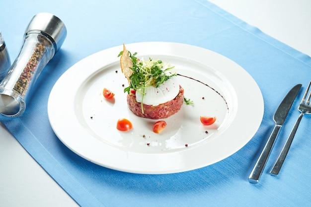 おいしい前菜-青いテーブルクロスの白いプレートにクルトン、ポーチドエッグ、ルッコラのサラダを添えた牛肉のタルタル