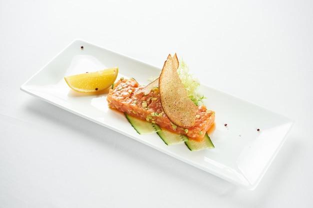 Вкусная закуска - тартар из лосося с авокадо и черной икрой на белой тарелке на синей скатерти.