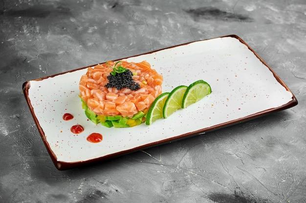 Вкусная закуска - тартар из лосося с авокадо и черной икрой на белой тарелке на сером столе.