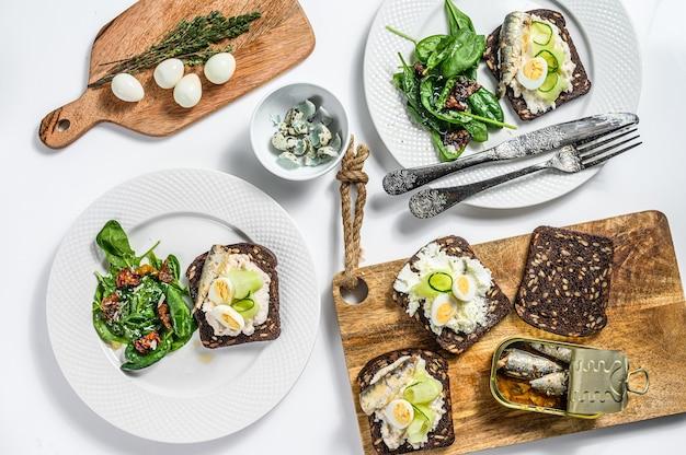 Вкусные закуски тапас, яйца всмятку и консервированные бутерброды с сардинами. салат со шпинатом и вялеными помидорами. белый фон. вид сверху.