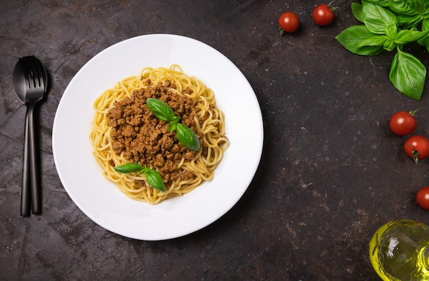 Delicious appetizing classic spaghetti pasta on a black background, top view