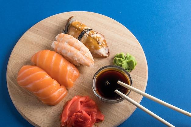 食欲をそそる美味しい握り寿司セットを木の板に醤油と箸でお出しします。フラットレイ