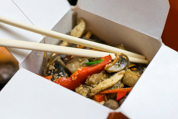 Delicious appetizing noodles with vegetables in cardboard box.