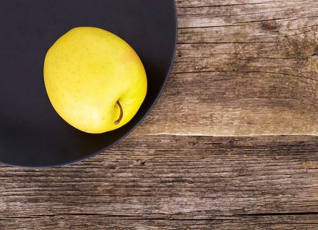 Вкусное яблоко на тарелке на деревянном столе