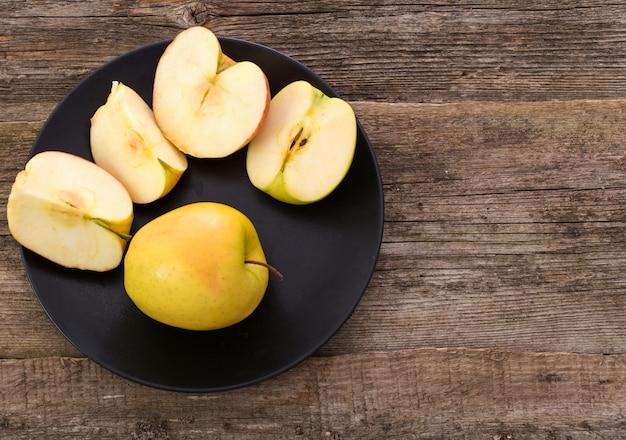 Вкусное яблоко на тарелке над деревянным столом