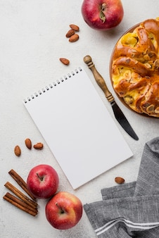 Delicious apple pie with notepad flat lay