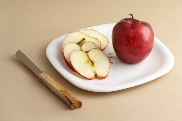 Delicious apple and slice in white plate with knife and fork