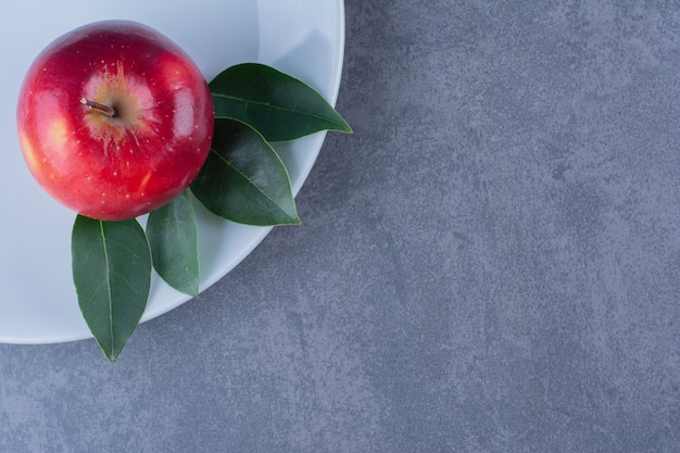 Вкусное яблоко с листьями на тарелке на мраморном столе.