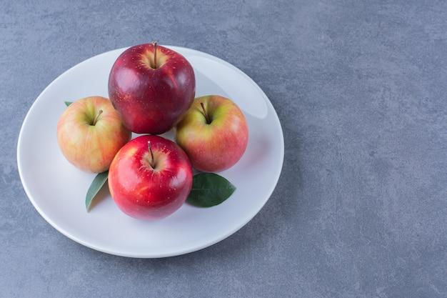 Вкусное яблоко с листьями на тарелке на темной поверхности