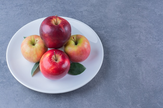 Delicious apple with leaves on plate on the dark surface