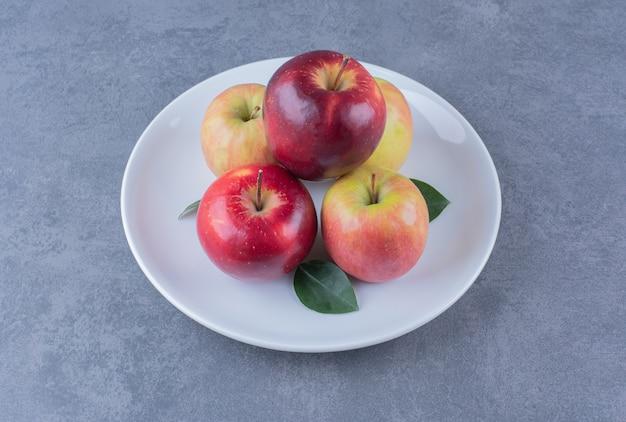 Deliziosa mela con foglie sul piatto sul tavolo di marmo.