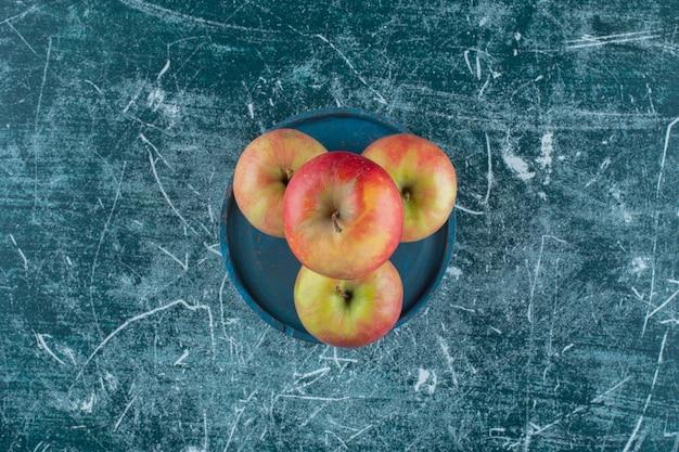 Вкусные яблоки на деревянной тарелке, на мраморном столе.