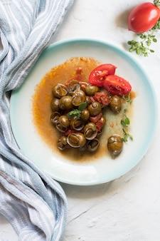 Delicious apulian snails called munaceddi with tomato sauce, oregano on a light table,
