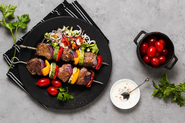 Delicious arabic fast-food skewers on black plate and tomatoes