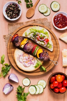 Delicious arabic fast-food veggies and meat on skewers flat lay