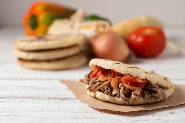 Deliziose arepas con carne e pomodori