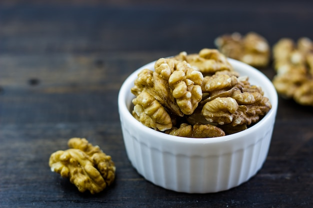 Delicious arrangement of walnuts in a bowl on a wooden table.