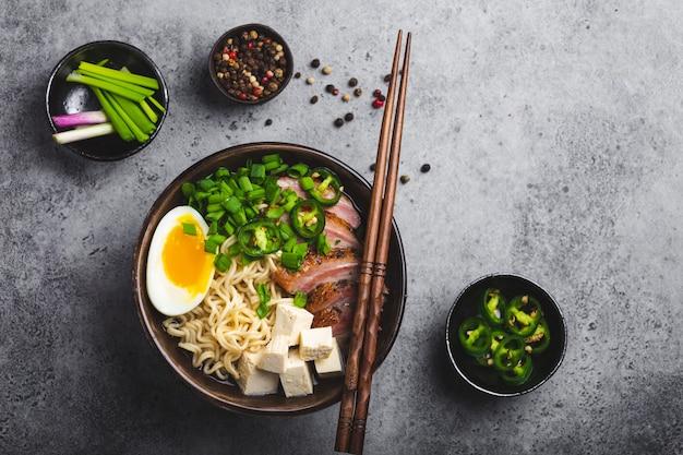 고기 국물, 두부, 얇게 썬 돼지고기, 노른자가 든 계란, 회색 소박한 콘크리트 배경이 있는 그릇에 맛있는 아시아 누들 수프 라면이 닫혀 있고 꼭대기가 보입니다. 저녁 식사 아시아 스타일을 위한 뜨거운 맛있는 일본 라면 수프