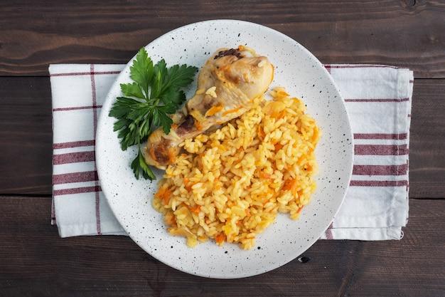 Вкусный азиатский плов, тушеный рис с овощами и куриная голень на тарелке. деревянный рустик. вид сверху
