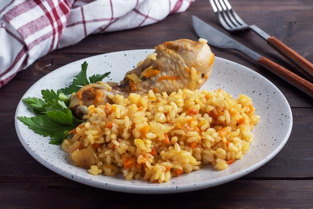 Вкусный азиатский плов, тушеный рис с овощами и куриная голень на тарелке. деревянный рустик.